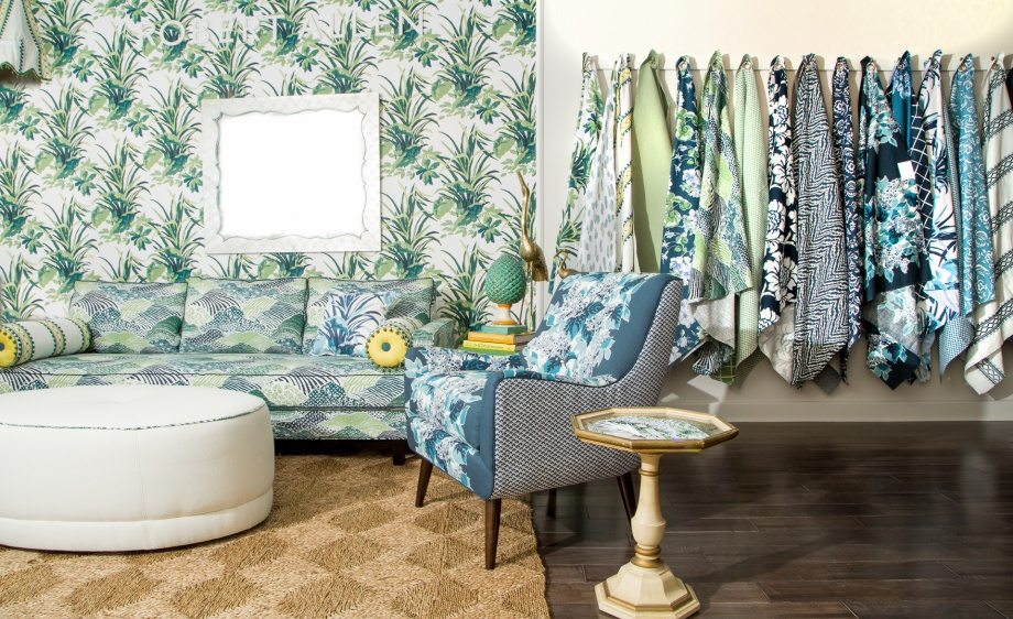 A lush landscape was created for the entrance of the Robert Allen @ Home Showroom in High Point using Bermuda Bay in Palm as paper-backed wallcovering. Fabrics in an array of blues and greens showcase the Madcap aesthetic of layering prints.